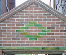 Pattern of green glazed brick against flat red bricks