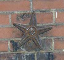 an iron star tie on the side of a brick building